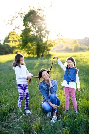 Mother with two small daughters having fun outdoors in spring nature.