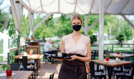Waitress with face mask serving customers outdoors on terrace restaurant.