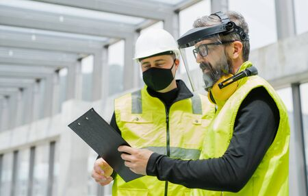 Portrait of workers with face mask at the airport, discussing issues.