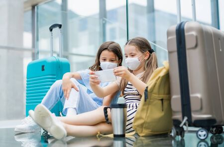 Small children with smartphone going on holiday, wearing face masks at the airport.