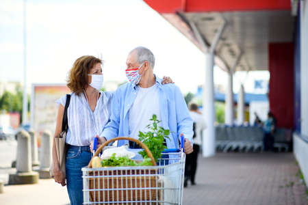 Senior couple with face masks and shopping walking outside supermarket in city. Stockfoto
