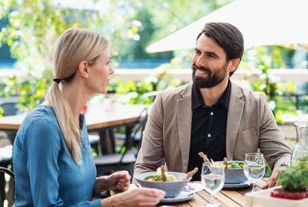 Happy couple sitting outdoors on terrace restaurant, talking.