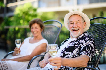 Senior couple holding wine outdoors on holiday, looking at camera.