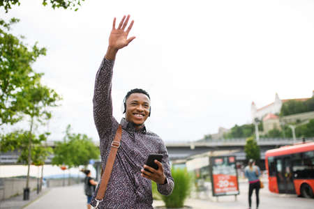 Cheerful young black man commuter outdoors in city, greeting somebody. 写真素材