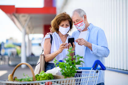 Senior couple with face masks and shopping with smartphone outside supermarket in city.