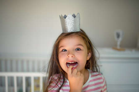 Portrait of small girl with princess crown on head indoors, looking at camera. 版權商用圖片