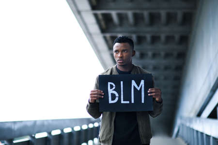 Man with BLM sign standing outdoors, black lives matter concept. Imagens