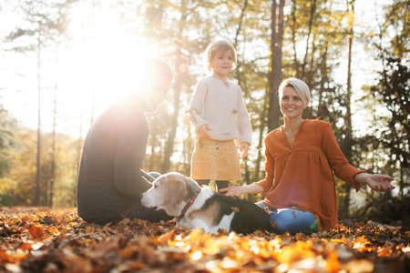 Beautiful young family with small daughter and dog sitting in autumn forest.