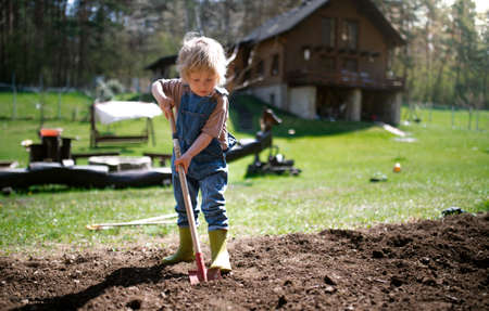 Small boy working outdoors in garden, sustainable lifestyle concept.