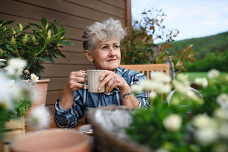 Senior woman with coffee sitting on terrace in summer, resting.