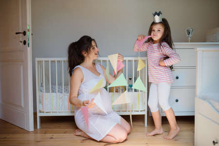 Portrait of pregnant woman with small daughter indoors at home, playing.