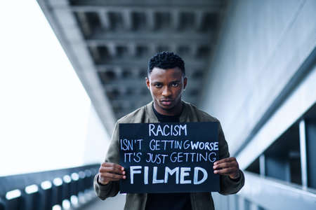 Man with written sign standing outdoors, black lives matter concept. Imagens