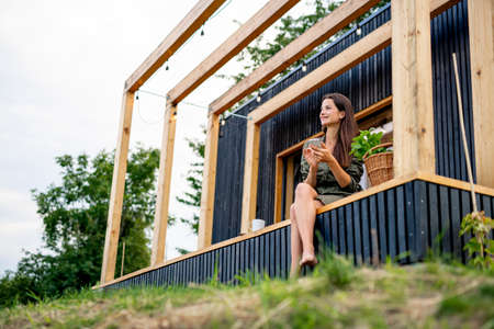 Young woman with smartphone outdoors, weekend away in container house in countryside.