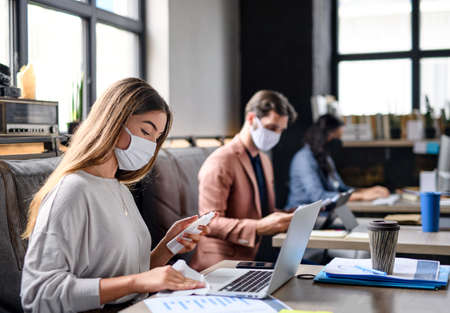 Portrait of young businesspeople with face masks working indoors in office, disinfecting laptop.