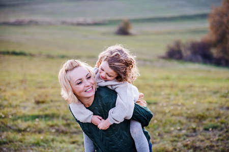 Small girl with mother on a walk in autumn nature, having fun.