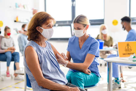 Woman with face mask getting vaccinated, coronavirus, covid-19 and vaccination concept. 스톡 콘텐츠