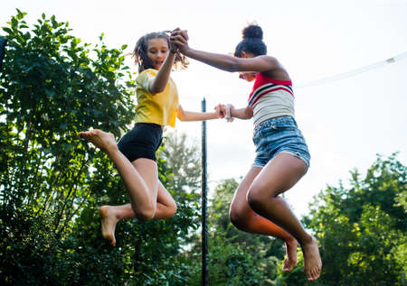 Low angle view of young teenager girls friends outdoors in garden, jumping on trampoline.