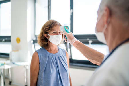 Doctor with face mask measuring temperature, coronavirus, covid-19, measuring temperature and vaccination concept. Stockfoto