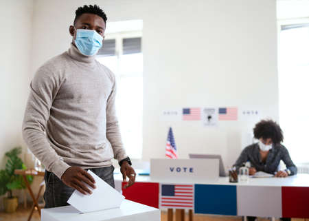 African-american man putting his vote in the ballot box, usa elections and coronavirus. Foto de archivo
