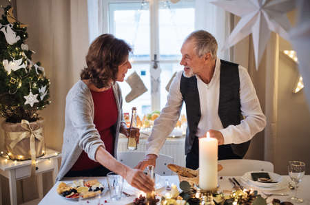 Happy senior couple indoors at home setting the table at Christmas. Standard-Bild