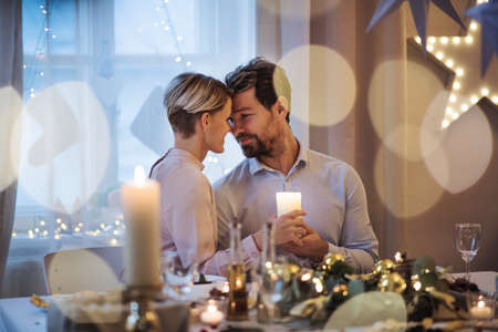 Front view of happy couple indoors at the table celebrating Christmas.