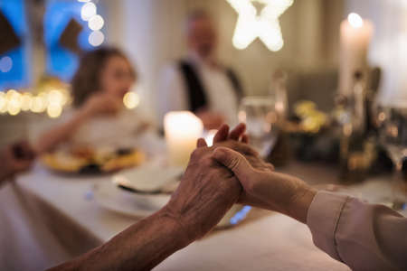 Close-up of hands holding together at the table at Christmas. Standard-Bild