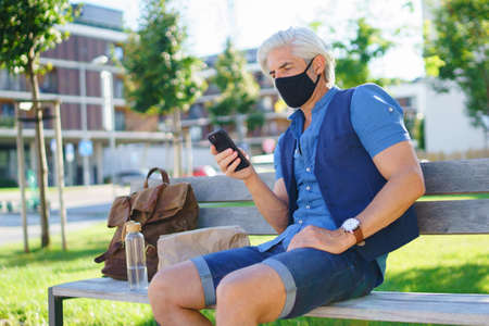 Portrait of mature man with face mask sitting outdoors in city, coronavirus concept. Standard-Bild