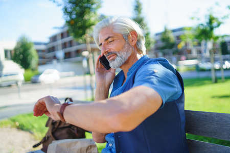 Portrait of mature man sitting outdoors in city, using smartphone.