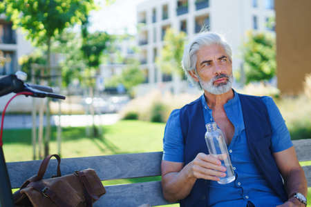 Portrait of mature man sitting outdoors in city, holding water bottle.