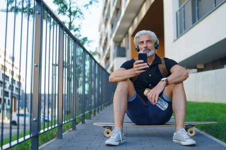 Portrait of mature man with headphones sitting outdoors in city, using smartphone.