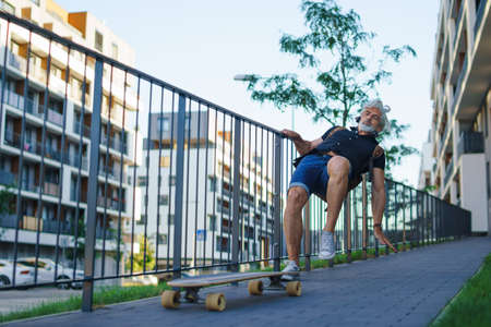 Mature man riding skateboard outdoors in city, falling down and accident concept.