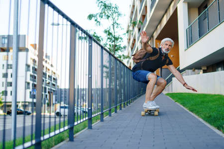 Portrait of mature man riding skateboard outdoors in city, going back to work.