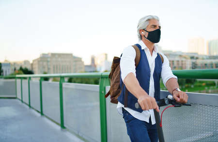 Mature man commuter with face mask and electric scooter outdoors in city, coronavirus concept.