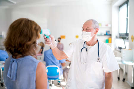 Doctor with face mask measuring temperature, coronavirus, covid-19, measuring temperature and vaccination concept.