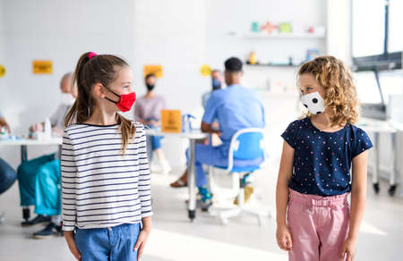 Portrait of small girls with face mask, coronavirus, covid-19 and vaccination concept. Standard-Bild
