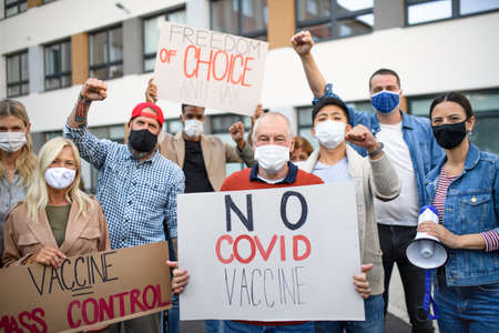 People with placards and posters on public demonstration, no covid vaccine concept.