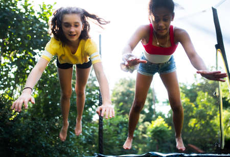 Front view of young teenager girls friends outdoors in garden, jumping on trampoline.