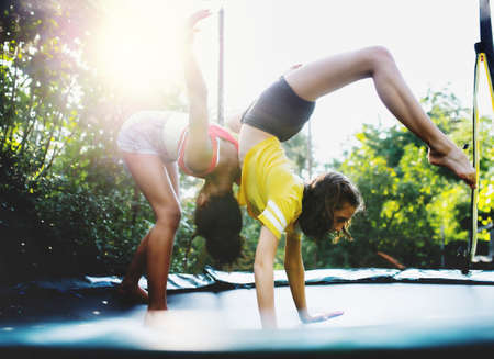 Front view of young teenager girls friends outdoors in garden, doing exercise on trampoline.