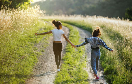 Rear view of young teenager girls friends outdoors in nature, running.