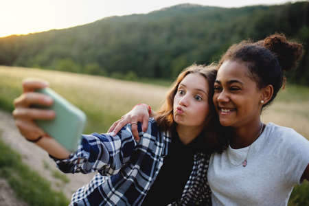 Front view of young teenager girls friends outdoors in nature, taking selfie.