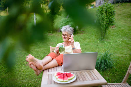 Happy senior woman with laptop and smartphone working outdoors in garden, home office concept.