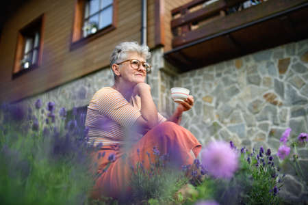 Portrait of senior woman sitting outdoors in garden, holding cup of coffee.