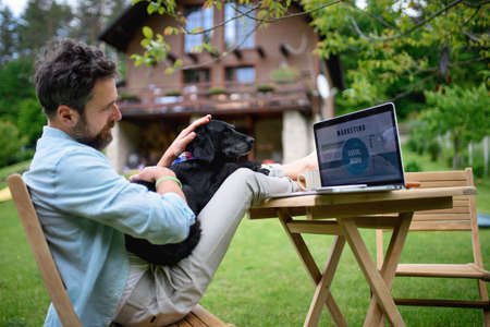 Mature man with laptop and dog working outdoors in garden, home office concept. Standard-Bild