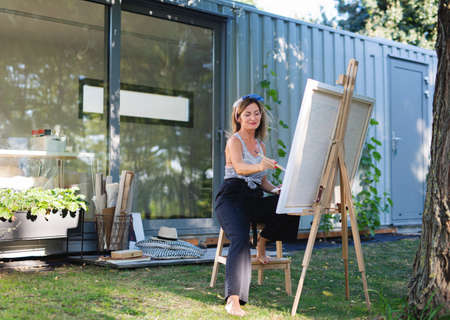 Portrait of mature woman with pallete painting outdoors in garden.