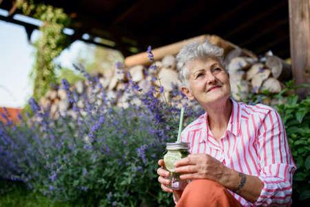Portrait of senior woman sitting outdoors in garden, holding lemonade drink.