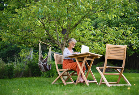 Senior woman with laptop working at the table outdoors in garden, home office concept.