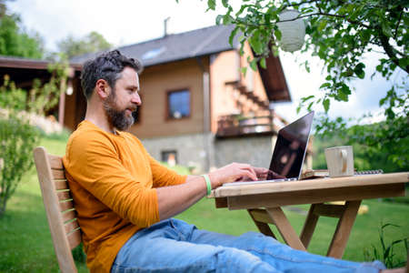 Side view of man with laptop working outdoors in garden, home office concept. Standard-Bild