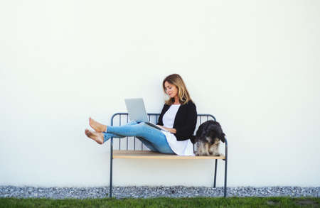 Mature woman with dog working in home office outdoors on bench, using laptop.