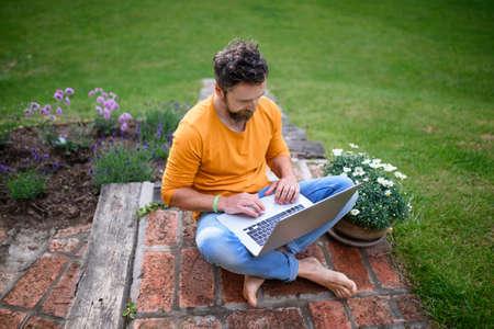 Mature man with laptop working outdoors in garden, home office concept. Standard-Bild