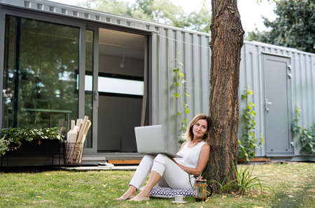 Mature woman working in home office outdoors in garden, using laptop.
